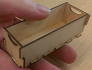 "photo of plywood box, about 3"" long, held in hand"